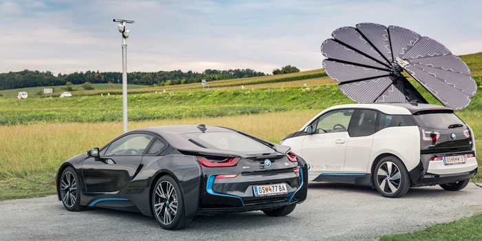 Two Electric BMWs Sit at a Charging Station Powered by a SmartFlower Solar Panel