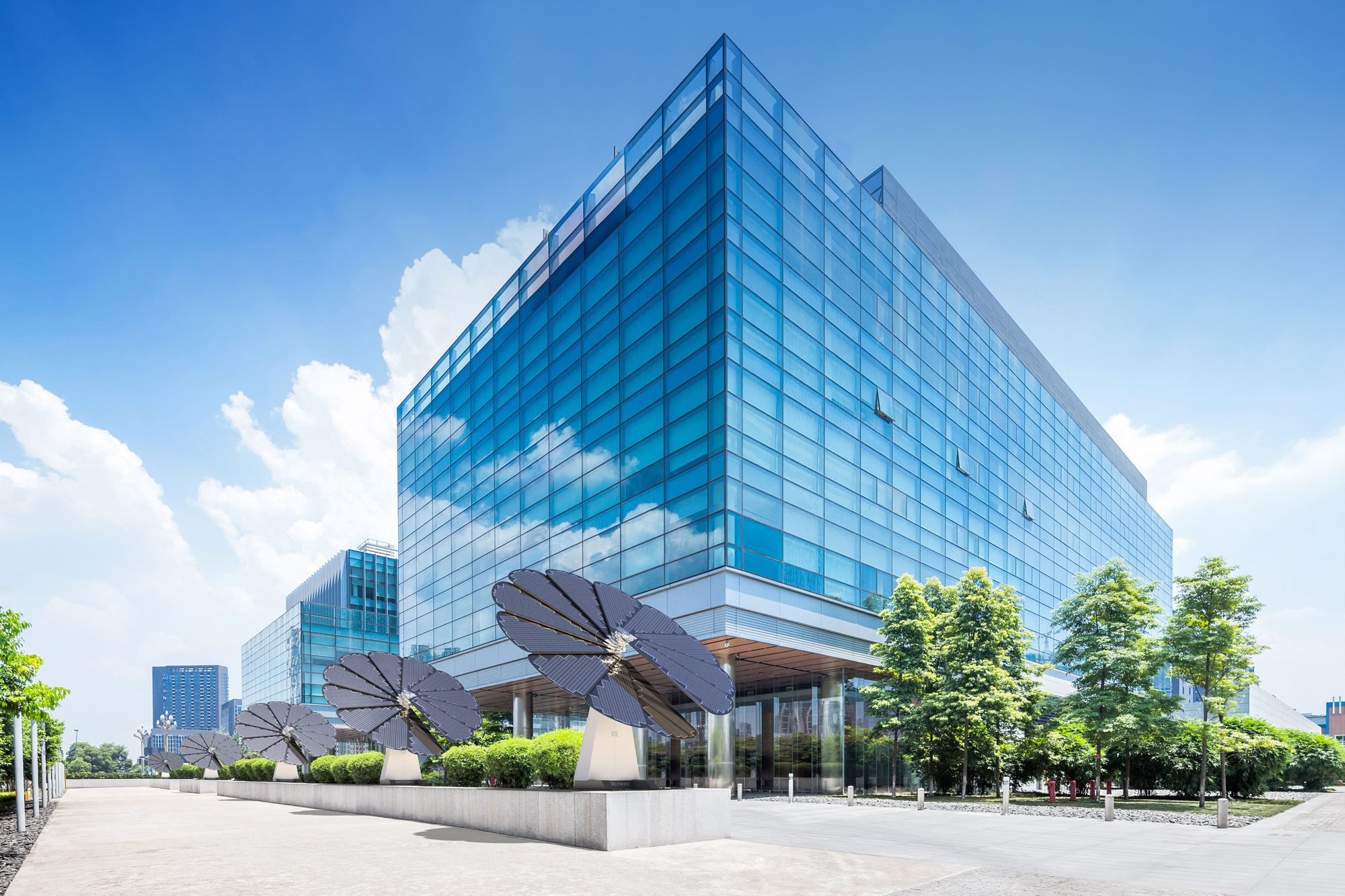 5 SmartFlower Solar Panels Line a City Street Next to a Glass Business Building