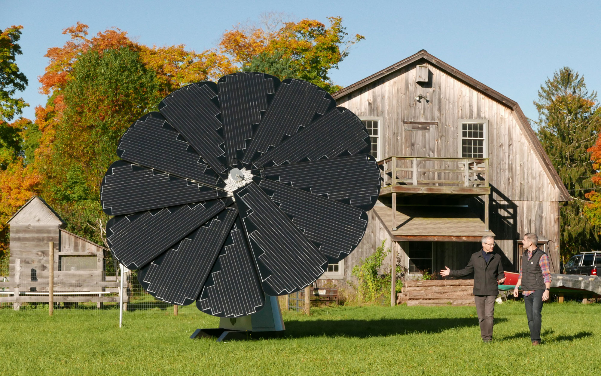 Two Men Stand Outside a Wooden Barn With a SmartFlower Solar Panel Out Front