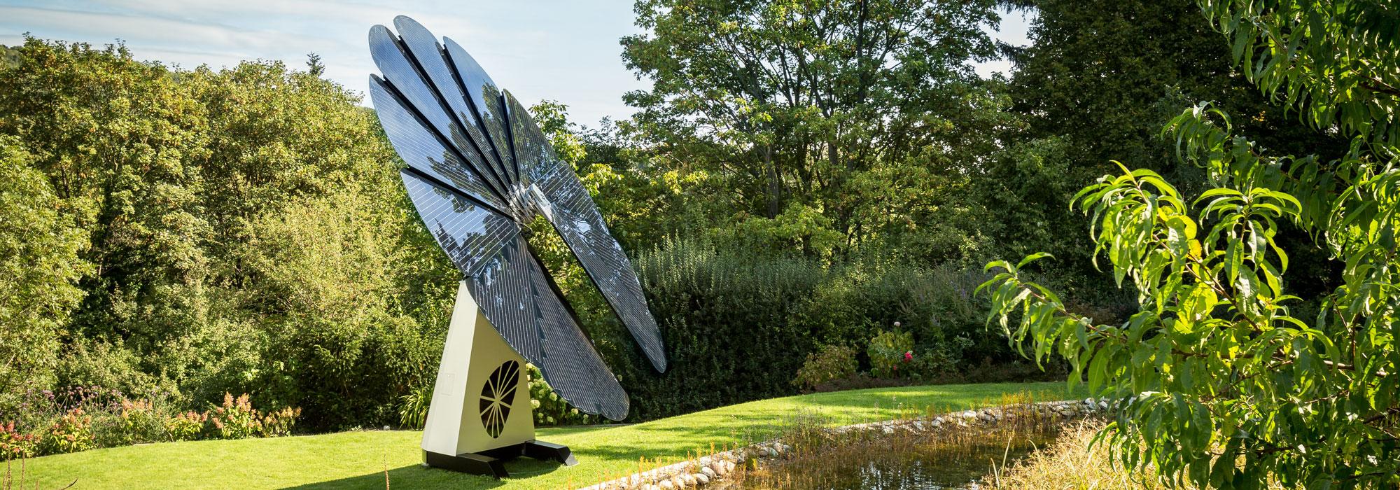 Um painel solar SmartFlower senta-se ao lado de um lago em uma pequena clareira forrada com árvores