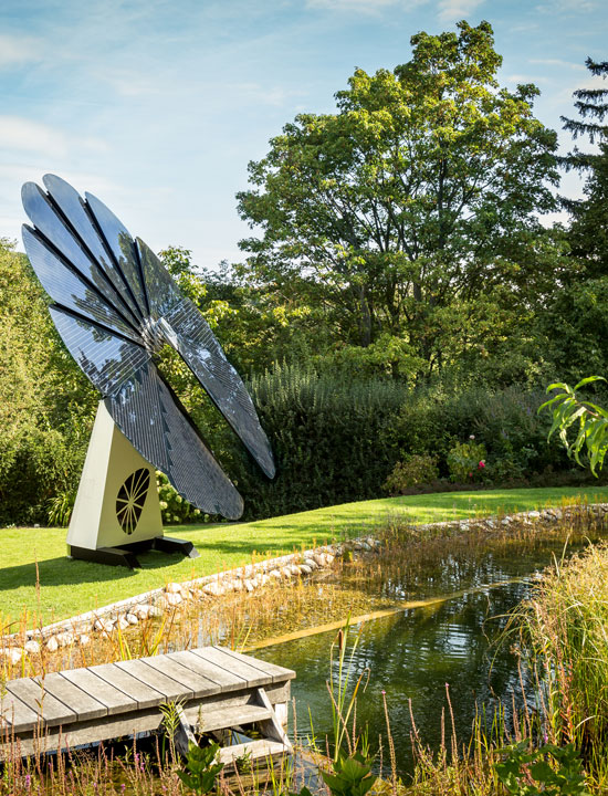 A SmartFlower Solar Panel Sits Next to a Pond in a Small Clearing Lined With Trees