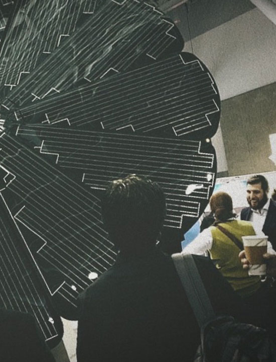 Spectators Examine a SmartFlower Installation at a Trade Show